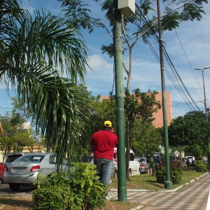 A man charges his phone using a wire dangling from a powerpole near a govenment building in the center of Asunción, Paraguay.